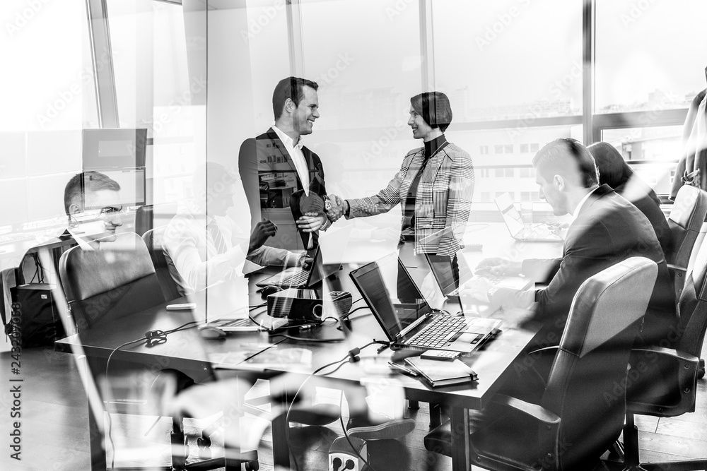 Fototapeta Sealing a deal. Business people shaking hands, finishing up meeting in corporate office. Business and entrepreneurship concept. Black and white image.