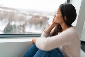 Winter seasonal affective disored SAD depression mood alone Asian girl feeling lonely - stress, anxiety, melancholy emotions. Sadness at home.