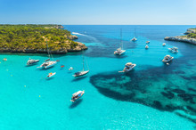 Aerial View Of Boats, Luxury Yachts, Green Trees And Transparent Sea In Sunny Bright Day In Mallorca, Spain. Summer Landscape With Bay, Azure Water, Beach, Blue Sky. Balearic Islands. Top View. Travel