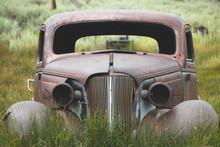 Old Rusty Car In Tall Grass