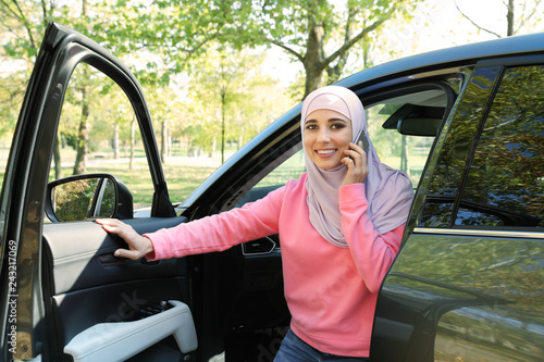 Muslim woman talking on phone near her car outdoors