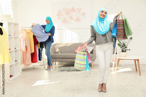 Muslim woman with shopping bags in modern shop