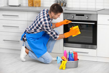 Man Cleaning Kitchen Oven With...