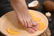 Woman Soaking Her Feet In Plate With Water And Orange Slices On Wooden Floor, Closeup. Spa Treatment