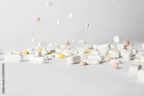Fotografia  Different pills falling on table against white background