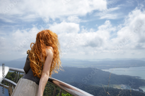 Photo Red Head Leaning on Metal Railing
