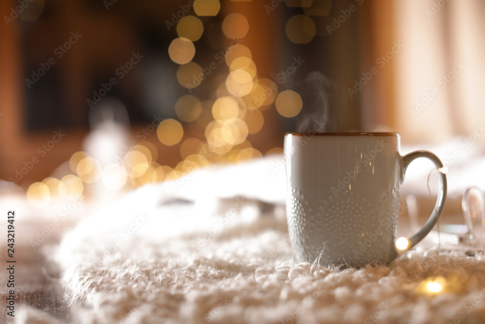 Fototapety, obrazy: Cup of hot beverage on fuzzy rug against blurred background, space for text. Winter evening