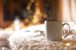 canvas print picture - Cup of hot beverage on fuzzy rug against blurred background, space for text. Winter evening
