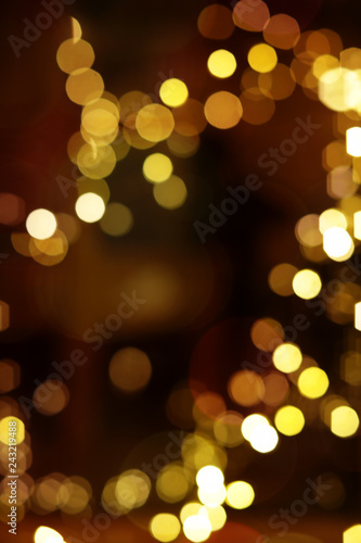 Blurred view of glowing lights on color background. Winter holiday