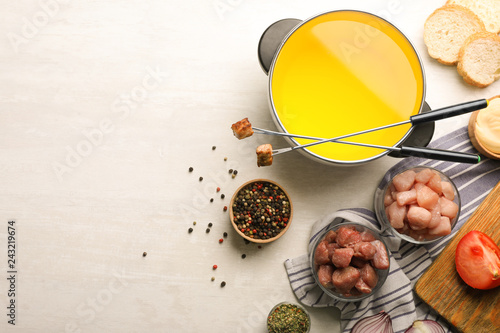 Flat lay composition with oil pot, meat fondue ingredients and space for text on light background