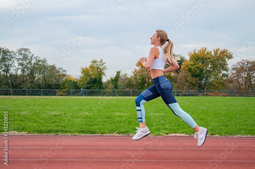 фотографія  Athletic woman running on athletics race track.