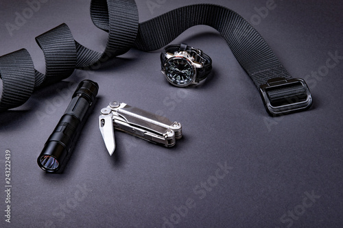 Fotografía  Everyday carry (EDC) items for men in black color - tactical belt, flashlight,  watch and silver multi tool