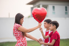 Little Boys Giving Balloon Heart To His Mother With Love