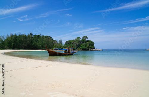 Obraz premium piękna sceneria z drewnianą łodzią na plaży biały piasek w błękitne morze i błękitne niebo na tropikalnej plaży.