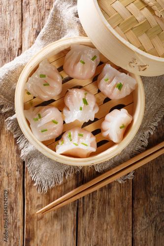 Dim Sum in bamboo steamer, Chinese cuisine. Closeup rustic. Vertical top view