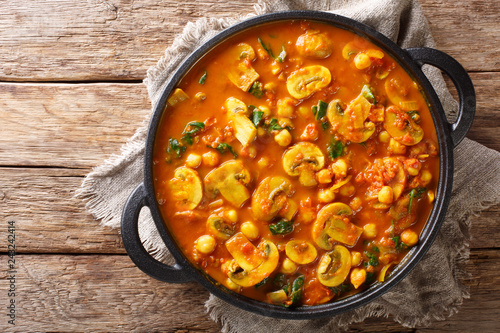 Mushroom curry with spinach and chickpeas close-up in a pan on the table Canvas Print