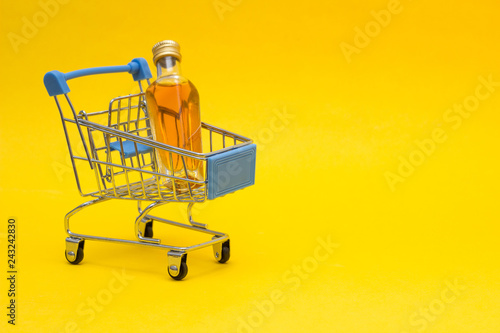 Cadres-photo bureau Bar Small bottle with alcohol in a shopping basket, close-up, copy space, orange background, consumerism