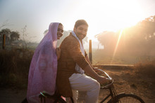 Side View Of A Happy Rural Couple In Traditional Dress Sitting On Bicycle In A Village With Agricultural Fields In The Background.