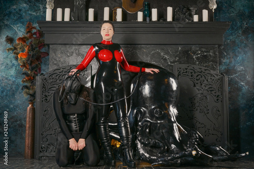 Valokuva  evil strong mistress with black hair wearing fetish latex catsuit and playing wi