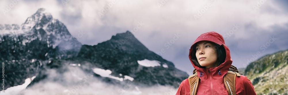 Fototapeta Hiker hiking in mountain range background banner - Asian woman mountain climber wearing hood jacket in rain - dramatic landscap in Switzerland alps.