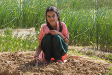Happy Little Rural Girl Digging Soil Using A Trowel Sitting In Agriculture Field.