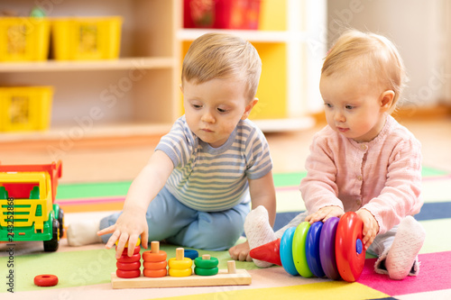 Preschool boy and girl playing on floor with educational toys Fototapeta