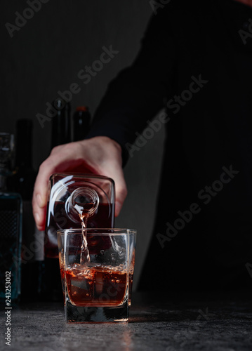 Barman pours whiskey in a glass at the bar.