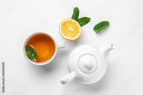 Photo sur Toile The Teapot, cup of hot beverage, lemon and mint on white background