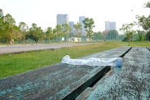 A Plastic Bottle Of Drinking Water Littering On Old Wooden Seat At The Outdoor Stadium At The Park With Blurred A Big Building And Green Nature Background For An Environmental Cleaning Concept