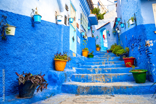 Deurstickers Beautiful view of the blue city in the medina of CHEFCHAOUEN, MOROCCO. Traditional moroccan architectural details and painted houses. street with flowers and bright blue walls with arch