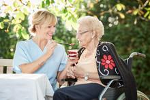 Pflegerin Hilft Seniorin Beim Essen