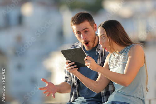 Fotomural Amazed friends finding online content on a tablet outdoors
