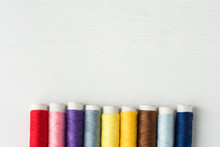 Row Of Multicolored Rainbow Palette Sewing Threads On Cardboard Spools. White Wood Background. Crafts Hobbies Local Artisan Business Interior Decoration Concept. Clean Minimalist Style Copy Space