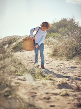 Boy With Basket Picking Up Garbage From Ground