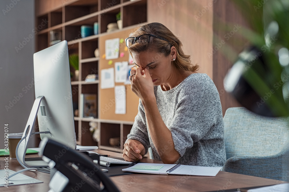 Fototapeta Business woman having headache at office