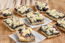 Shortbread Cookies With Blueberry Jam On Baking Paper On Wooden Background.