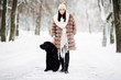 beautiful young girl with black hair in fur coat and hat in winter is resting on the street, a woman playing with big dog on snowy frosty day