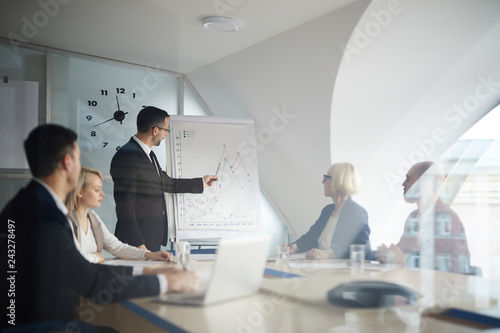 Fotografía  Confident businessman in formalwear standing by whiteboard and pointing at graph