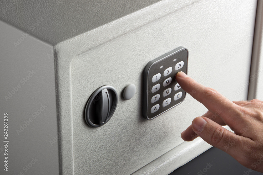 Fototapety, obrazy: the hand opens a combination lock on the safe, a light safe on a dark background