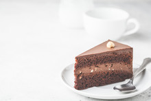 Piece Of Chocolate Cake On White Plate, White Background. Vegan Dessert, Plant Based Food Concept.
