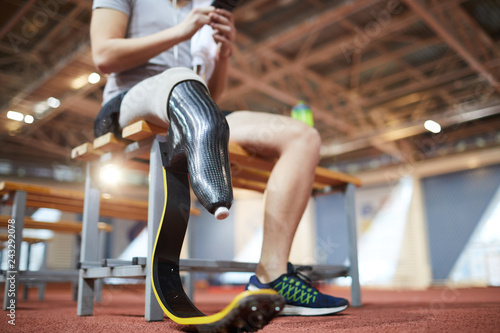 Handicapped right leg of young paralympic sportsman having break after training Wallpaper Mural