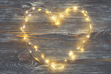 Garland Lights In The Shape Of Heart On A Rustic Wooden Table. Concept Of Love And Valentine's Day