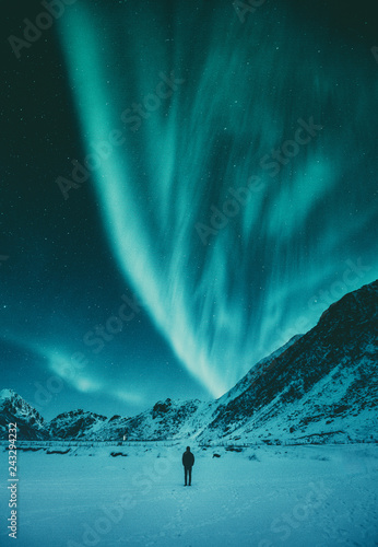 Photo sur Toile Aurore polaire Young man watching Aurora Borealis in winter, Lofoten, Norway