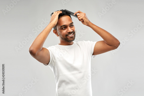 Leinwand Poster grooming, hairstyling and people concept - smiling young indian man brushing hai