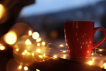Cup Of Hot Beverage On Balcony Railing Decorated With Christmas Lights, Space For Text. Winter Evening