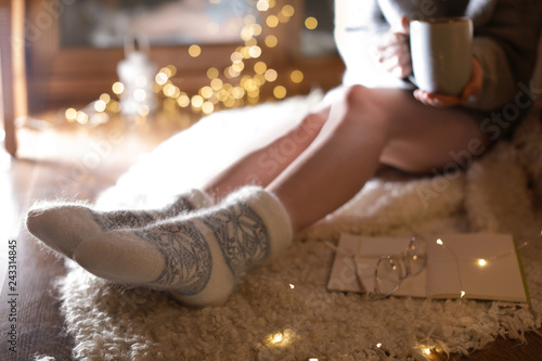 Foto auf AluDibond Schokolade Woman with cup of hot beverage and book at home in winter evening, closeup