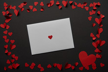 Top View Of White Greeting Card With Frame Made Of Red Paper Cut Hearts On Black Background
