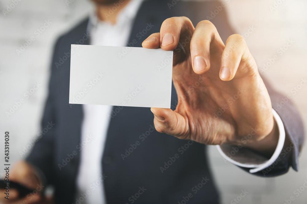 Fototapeta businessman hand showing blank white business card closeup