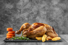 Roasted Chicken, Potatoes And Vegetables On Dark Plate. Side View
