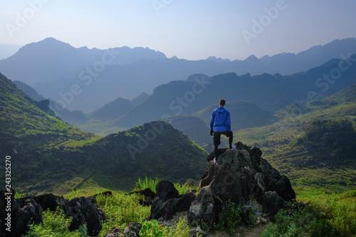 Fototapeta Backpacker standing on outcrop overlooking karst mountain scenery in the North Vietnamese region of Ha Giang / Dong Van obraz na płótnie